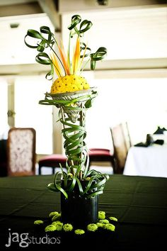 Centerpiece featuring yellow button mums, birds of paradise, lily grass