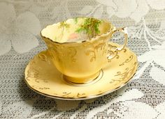 An elegant yellow Aynsley cup and saucer adorned with Blue Bell woodland scene and dramatic hand painted gold gilt. Breathtakingly beautiful!