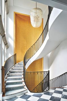 This is how you make an entrance: with a gold wallpaper focal point and a spiral staircase.