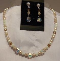 LS7013 ...SET... Necklace and Earring Set in gold and white glass pearls, with accents of Swarovski amber and clear round crystals and clear square crystals. The earrings are approximately 2 inches long on silver filigree posts and the necklace is approximately 21 inches long with a silver closure. These beautiful pieces are perfect for the bride on her wedding day.