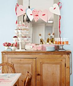 Set a pretty Valentine's buffet with champagne, cookies, nuts and more. Ideas for Valentine's decorating: http://www.midwestliving.com/homes/seasonal-decorating/easy-valentines-day-decorations-and-gifts/?page=8