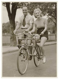 Man and woman on a Malvern Star abreast tandem bicycle, c. 1930s.