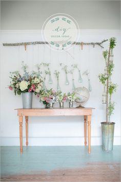 Tak aan de muur en dan allemaal flessen of potjes met bloemen er aan binden.