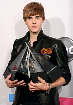 Justin Bieber and his armful of trophies at the 2010 American Music Awards.