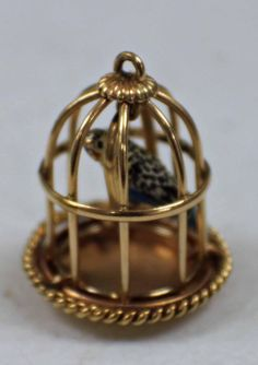This 14k yellow gold birdcage charm is in good condition. This charm features a bird that resembles a blue parakeet sitting inside on the birdcage