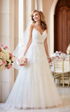 "This lace and tulle A-line wedding dress by designer Stella York features a low V-neck bust and back, spaghetti straps, and Diamante beading throughout. The back zips up with ease under fabric-covered buttons. A 1"" Diamante-encrusted grosgrain ribbon belt accentuates the waist."