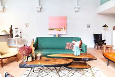 Living room with a green love seat, reclaimed wood coffee tables, and a large Moroccan rug
