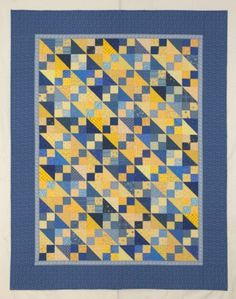 This is a Texas Two-Step Quilt based on color.  For this quilt to work all of the blue fabrics need to be darker in value than the yellows.  The half-square triangles and four-patches used in the blocks came from a swap.