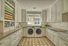 Amazing dual laundry room / craft room ~ love the white cabinets and built-in gift wrapping center! Adding built-in sewing cabinets would be heavenly.