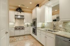 Loving this white kitchen with slab granite backsplash all the way up to the upper cabinets