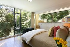 A corner #bedroom's floor to ceiling windows allow sunlight to stream in, while the mature #trees help maintain privacy.