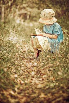 Ein Kind sitzt draußen und liest.