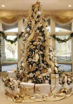 Christmas tree, very regal looking with gold and pretty presents under the tree.