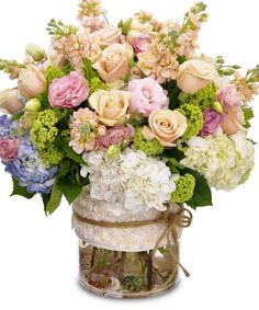 Elegant Abundance - This assortment of premium flowers is sure to impress the recipient! A combination of flowers that includes hydrangea, roses and lisianthus is arranged in a cylinder vase. #KittelbergerFlorist #RochesterFlowers