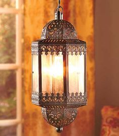 The lantern style of the Hanging Pendant Lamp gives any room an exotic flavor. Glass panels are bracketed by a metal frame that's adorned with lacy cutouts and scrollwork. Suspend it from the ceiling by the sturdy 6'L link chain. In-line on/off switch on