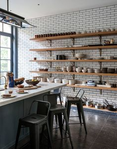 painted brick walls. bar table and stools. light shaded wooden shelves with darker supports. colour contrast working well