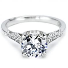 This stunning engagement ring is pictured with a round brilliant-cut center stone.  Bold prongs and graduated diamond shoulders amplify the center stone.  The side view is accented with fresh, pretty diamond details.