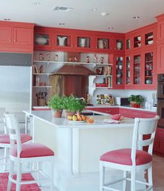 You can't help but smile in this vibrant coral beach house kitchen. - Traditional Home ® / Photo: William Stites / Design: Betsy Speert