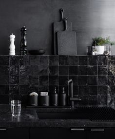 The kitchen has two handmade backsplashes a row of handglazed glossy black Moroccan Clé tile and a bleached metal steel wall surroundan effect Hollis developed wit.