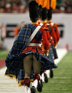 Windy down there? Band member flashes his bum as his kilt is blown up