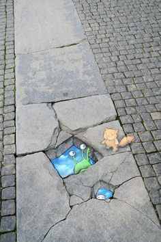 Sluggo encounters a rare double skyhole in Borås, Sweden. Luckily, the locals are quick with a helping hand (or paw, or whatever that is). (September 10, 2015) - street art by David Zinn