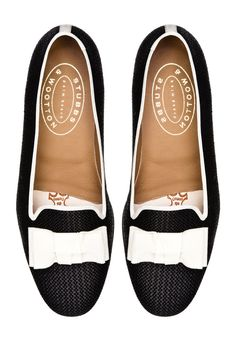 """Our Bow slipper features a Black Woven Straw Upper with a White Grosgrain Trim and Bow. Meticulously Hand-crafted in Spain. Leather lined to provide additional support and comfort. The stacked wooden heel is ¾"""" in height. Leather soled. True to American sizing."""