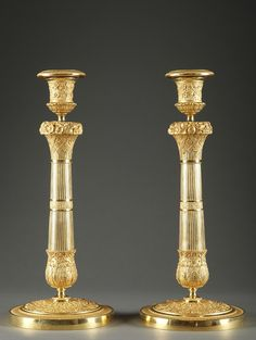 A fine pair of gilt bronze candlestick resting on a circular base adorned with various flowers and a frieze of water leaves. The flared, partially fluted stem is chiselled with small flowers, lattice and foliage. The socket finely decorated with foliate garlands of flowers and ribbons rests on a wreath of fruits and flowers, a very fashionable pattern under the French Restoration. The removable nozzle is decorated with water leaves. Circa :1820
