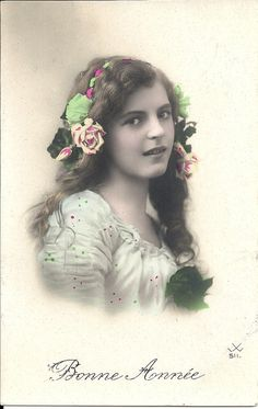 Long hair girl, floral headband, pink blue green, beautiful girl, real photo card, Edwardian child, teenage girl, hand coloured. Estimated date c.1910s.  A great item for collectors, or to include in a scrapbook, journal, or other altered art project.  Used: The card has been written on and bears a partial frank mark.  Condition: Good condition with some corner/edge wear, light album marks, small corner creases to both bottom corners, light surface wear and some soiling (including glue&...