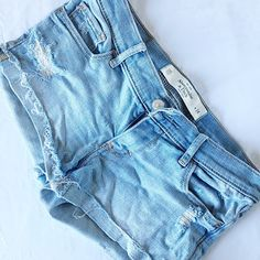 """LIGHT WASH DENIM CUT OFF SHORTS DESTROYED Low rise Fold over bottom cut off Slightly destroyed Light wash  Color: Blue  Size: 00  Condition: Good - worn a couple of times Washed a couple of times.   Material: 83% Cotton 16% Polyester 1% Elastane  Measurements: LENGTH: 8"""" WAIST: 24"""" FRONT RISE: 6"""" BACK RISE: 11"""" INSEAM: 2""""  No stains, rips, tears 