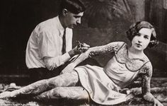 Keeping her calm: A woman lays on her side as a man completes her full body suit during th...