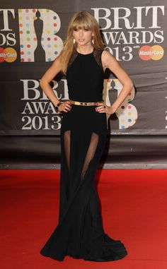 Taylor Swift shows a little leg in a sleek Elie Saab gown featuring sexy sheer skirt panels at the 2013 Brit Awards. A gold ridged belt cinches the singer's waist.