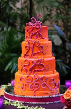 Beautiful bright orange cake set over four tiers with pink icing scrolls...