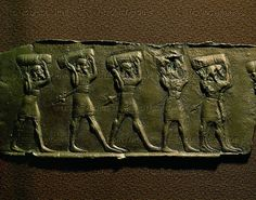 ASSUR RELIEF 10TH-6TH BCE Men carrying goods, cover of a wooden door. Fragment of a bronze sheet (858-824 BCE) from the palace of Shalmaneser III. Yeni-Assur (Tell Balawat), Mesopotamia (Iraq) British Museum, London, Great Britain
