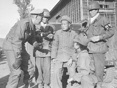 Captain Warren J. Rosengren interrogates a captured Chinese soldier near Kunang in North Korea. South Korean military policemen stand guard while an interpreter translates.