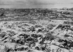 A winter view southeast (after the Battle?) from over the settlement of central Stalingrad, northwest of the railyard.  Dark shadows mark the Krutoi Ravine at upper left; the small ravine at bottom left feeds into it.  Beyond the railyard:  the L-shaped (apartment) house, the Railwaymen's Building, the flour mill (with its separate smokestack left of it), and Pavlov's House.  Stalingrad Aerial Scans (online) photos GX2839-568 and -570 show this area after the snow had melted.