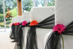 Chair covers & blacks sashes with fresh colourful gerberas from The Event Dressers