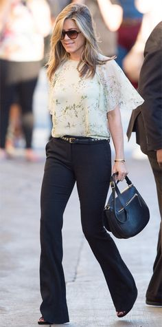 Dark flared jeans, with breezy floral blouse and studded skinny belt.    Jennifer Aniston
