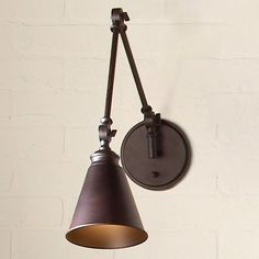 """This classic adjustable swing arm wall sconce, with a traditional jointed arm capped in a sleek cone shade, merges style and functionality for the perfect task lighting solution for refined spaces. Available in English Bronze, Polished Nickel, Satin Nickel, and Warm Brass finishes. 60 watt max medium base socket. (16""""Hx6""""Wx13-33.75"""" extended). Moves up and down and side to side. Supplied with Cord & Plug, and Hardwire. Backplate 6""""."""