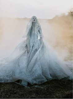 An eerie bride, like a spectral version of Miss Havisham from the novel Great Expectations by...