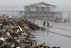 Bicyclists ride past debris stacked on a seawall road in Galveston, Texas, on September 14, 2008.