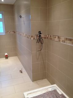 300x600 porcelain wall and floor tiles with polished marble border and chrome listellos.