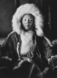 This portrait of a young girl illustrates both the beauty of and the importance given by the Nenets to their clothes. Her main coat is made of the inside of reindeer skins, while her hood is made with the fur of blue fox.