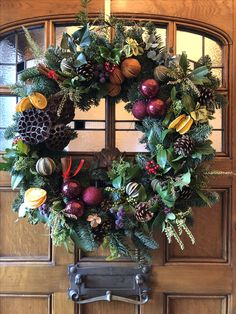 "Made using cones & greenery from my garden, dried citrus fruits and baubles on a shop bought 18"" spruce wreath"