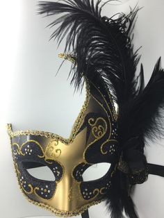 Black and gold feathered Mardi Gras mask with ribbon ties.
