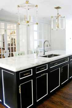 A Dated Kitchen Gets a Stunning Modern Makeover// black kitchen island, lucite pendants, french doors, mirrored cabinets
