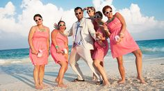 Groom and bridesmaids show some attitude for photo shoot on the beach. Pink bridesmaid dresses, turquoise jewelry and white sunglasses. | Palace Resorts Weddings ®