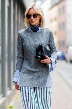 Street style look com blusa cinza, camisa azul e saia listrada.