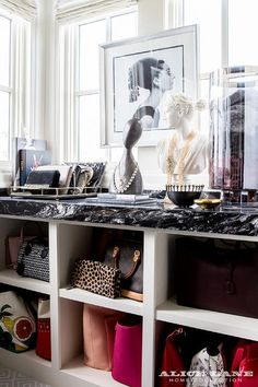 The Ivory Lane - Glam closet features a built in shelving unit filled with designer bags topped with black marble lined with a glass hurricane holding a collection of scarves, gray bust necklace holder, White Diana Bust, Rowena Sculpture and Ritter Tray placed under windows lined with an Audrey Hepburn print.