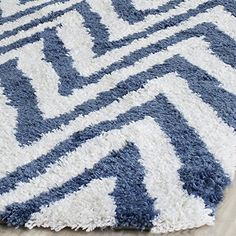Safavieh Chevron Shag Collection SG250A Handmade Ivory and Blue Shag Area Rug, 6 feet by 9 feet (6′ x 9′) #handmade Spark up a bedroom or family room with the striking Chevron Shag rug from Safavieh. Hand-tufted of exceptionally soft acrylic pile in combinations of white with fashion colors, these rugs update contemporary and transitional interiors with bold pattern and lush texture. The handmade and hand-woven construction add durability to this rug, ensuring it will be a favorite f..