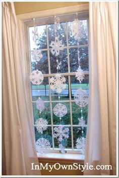 snowflake decoration.    great idea to use a tension rod inside the window to hold the decorations. no holes or hooks needed!